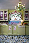 Dramatic, vintage kitchen with pink accessories and lino flooring designed to look like tiles