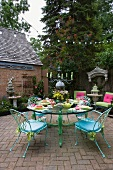 Garden terrace with delicate, pastel blue garden chairs around round glass table with pastel green metal legs