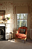 Rococo armchair in front of window and stencilled patterns on wall in traditional room with fireplace