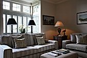 Sofa with striped upholstery in front of bay window in rustic ambiance