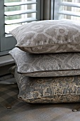 Stack of patterned cushions in bay window with Venetian blinds