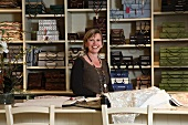 Fabric shop - woman standing in front of pattern books on shelves and sample books on counter