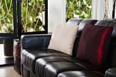 Leather sofa with red and white throw pillows