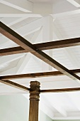 Detail of wooden bed posts and white ceiling beams