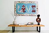 Holzbank mit Dekoartikeln und Büchern unter einem Wandteppich mit LOVE Schrift