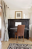 Black upright piano in home