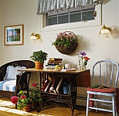 Books and flowers on table, wicker armchair and chair on veranda