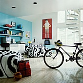 Boys' room with blue wall, black and white bedspreads, desk and bike