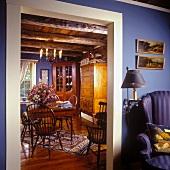 Blick neben einem Ohrensessel in das Esszimmer mit antiken Windsor Stühlen, Kommode und Eckschrank