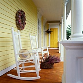 Two rocking chairs and a basket of heather on a yellow-painted veranda