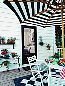 White terrace with table, chairs, parasol, plants and black and white chequered floor