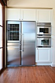 Stainless steel fridge surrounded by cabinets