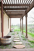 Pathway of rough stone slabs below pergola running along house with view of countryside