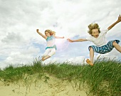 Children playing on grassy sand dune