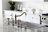 Chrome faucet and apron kitchen sink in contemporary kitchen