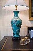 Tischlampe mit chinesisch bemaltem Vasenfuss auf Schreibtisch im Antikstil mit goldgeprägter Ledereinlage
