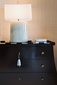 Dresser with a lamp and books on top