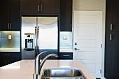 Unterbauspülbecken in modernem Küchenblock und Edelstahlkühlschrank im Hintergrund