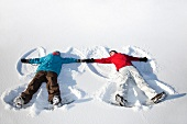 Couple making snow angels outdoors