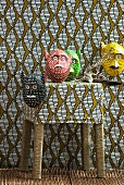 Colourful animal masks on stool and on wall covered in patterned fabric