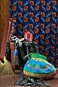 Brightly striped crocheted bag in front of stool and African-style floral wall hanging