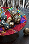 Wooden balls with carved patterns in wooden dish covered in colourful fabric scraps