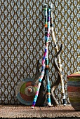 Colourfully painted sticks and baskets against patterned wall hanging