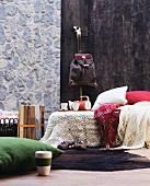 Häkeldecke und Wolldecken auf einem Bett vor Paneelen in Steinwand- und Holz-Optik