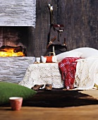 Crocheted and woollen blankets on bed next to fireplace