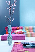 Combination of floor cushions in pastel shades against blue wall; artistic floor vase of Japanese cherry blossom in foreground
