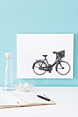 Bicycle motif made from pins and thread on white background on light blue wall