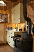 Old stove in kitchen of rustic wooden cabin