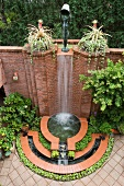 Arrangement of fountains and waterfall against high brick wall in courtyard