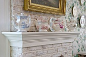 Collection of antique teapots on mantelpiece against brick chimney breast