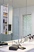 Contemporary wash stand in front of mirrored wall with integrated cabinet