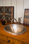Old, hammered metal wash basin with vintage tap fitting in wooden base unit