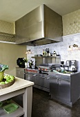 Stainless steel kitchen counter with extractor hood and simple kitchen table