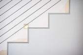 Detail white staircase and wire railing
