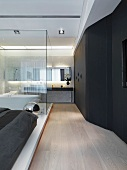 Modern bathroom inside bedroom with glass wall