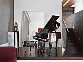 Open grand piano in home near staircase