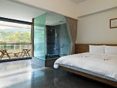 Modern bedroom with glass shower and outdoor patio