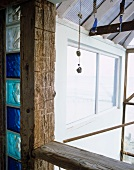 Balkontragwerk aus Holzbohlen mit integriertem Streifen aus blauen Glasbausteinen