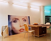 Loft-style interior with dining table and chair in front of enormous picture leaning on wall