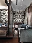 Graue Couch in einem luxuriösen Schlafzimmer mit Doppelbett auf einem Podest aus Edelholz; im Hintergrund eine gemusterte schwarz-weisse Wandtapete