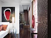 Wohnraum mit einem Fussboden aus Edelholz und modernen Kunstobjekten