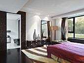 Großräumiges, modernes Schlafzimmer mit großem Doppelbett und einem gemusterten Teppich