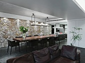 Gediegener Essbereich mit großem, massivem Esstisch, einer rustikalen Natursteinwand und einem originellen, hängenden Kerzenhalter