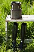 An arrangement of a milk churn and black boots