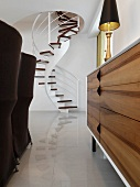 Straight on view of modern spiral staircase through furniture