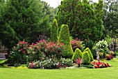 Elegant gardens with stone statue and luxuriantly flowering plants